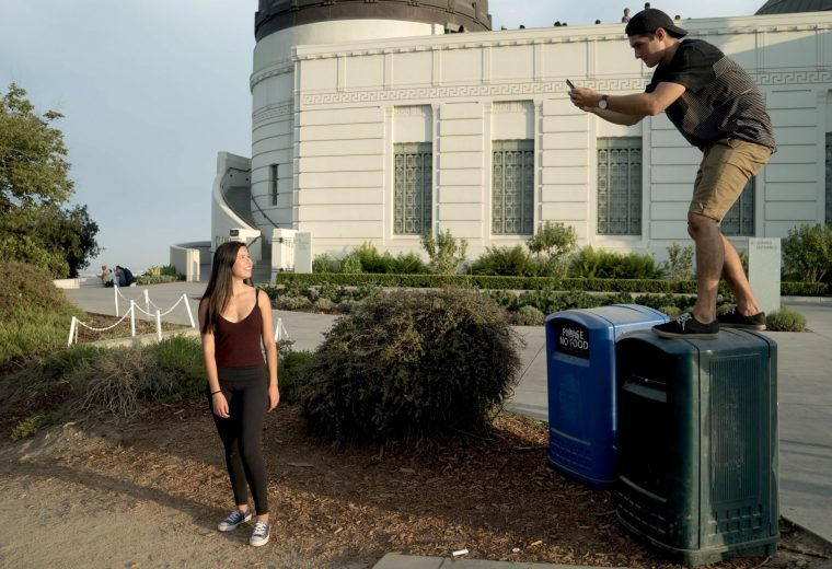 A photo of a man standing on a trash can with a cameraphone, so he can take a photo of a woman from a higher height.