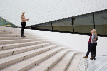 An older woman photographs a couple from the top of a flight of stairs.