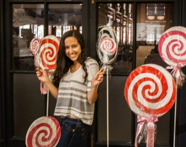 A photo of a smiling woman posing amidst gigantic lollipops. She looks small.