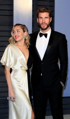 Two celebrities photographed on the red carpet in the classic couple pose.