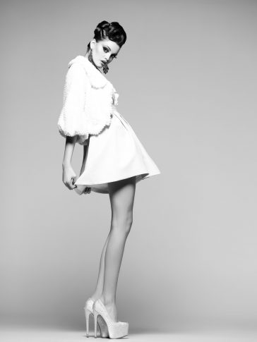 A model posing in a short white dress and white high heels, with long legs, looking down towards the camera.