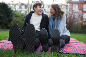 A photo of a man and a woman on sitting on a picnic blanket in a park, with their feet towards the camera. Their shoes appear massive.
