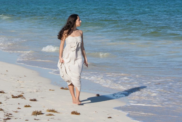 A woman walking on a beach next to the ocean. Her size is hard to determine.